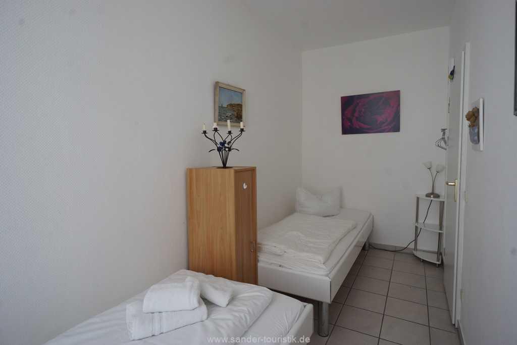Schlafzimmer mit zwei hintereinander gestellten Einzelbetten
