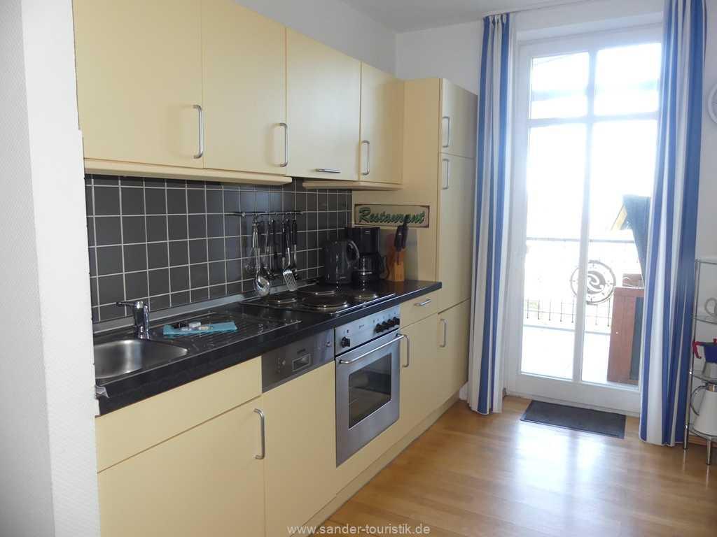 Räumlich abgetrennte gut ausgestattete Küchenzeile mit Spülmaschine