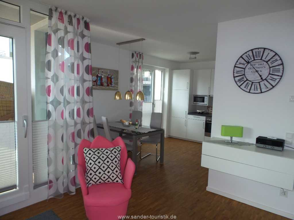 Blick vom Wohnbereich auf die offene Küche und davor plazierten Essbereich - DünenResort